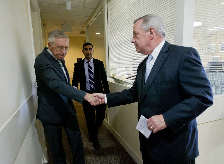 Senate Minority Leader Harry Reid of Nev., left, shakes hands with Senate Minority Whip Richard Durbin of Ill.,, right, after speaking with reporters following the Senate vote on the Iran nuclear agreement on Capitol Hill in Washington, Thursday, Sept. 10, 2015. Senate Democrats voted to uphold the hard-fought nuclear accord with Iran on Thursday, overcoming ferocious GOP opposition and delivering President Barack Obama a legacy-making victory on his top foreign policy priority. (AP Photo/Pablo Martinez Monsivais)