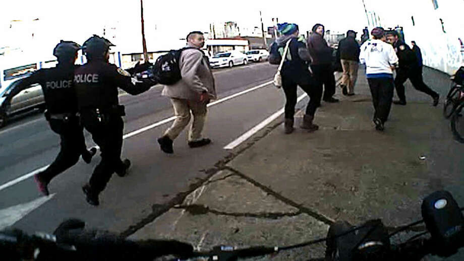 In this image from video from a Seattle police body camera video, Seattle police officers move in to make an arrest during a Black Lives Matter demonstration in January 2015. Under a pilot program, 12 officers wear body cameras and blurred videos are released online. The use of police body cameras is spreading to keep officers honest about using force against citizens. But how and when the public gets to see the footage is up for debate. (Seattle Police Department via AP)
