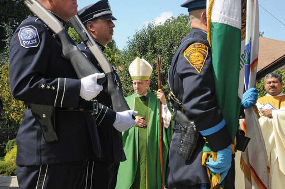 Bishop Frank J. Caggiano greets police and rescue workers Sunday at St. Matthew Church where the annual Blue Mass commemorating the 14th annivesary of 9-11 was held. Hour photo/Matthew Vinci