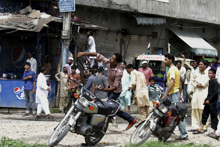 One of the supporters of Pakistan's ruling party throws a rock on a procession of cricketer-turned-politician Imran Khan in Gujranwala, Pakistan, Friday, Aug. 15, 2014. Dozens of members of Pakistan's ruling party threw stones and shoes at a truck carrying a popular opposition leader Khan Friday, as he was on the road for the second day to travel to the capital, Islamabad, for a rally meant to pressure the country's Prime Minister Nawaz Sharif to resign over allegations of rigging last year's parliamentary elections. (AP Photo/K.M. Chaudary)