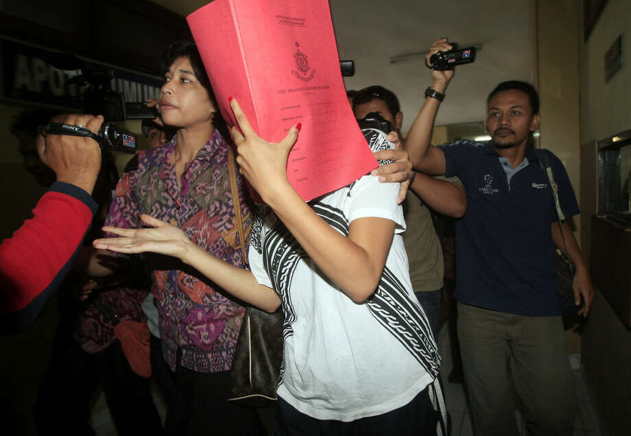 Heather Mack, covering her face, is led to a hospital for a medical check by Indonesian police officers in relation to the death of her mother Sheila von Wiese-Mack in Bali, Indonesia, Friday, Aug. 15, 2014. The body of the 62-year-old American woman was found stuffed inside a suitcase on the Indonesian resort island of Bali, and authorities on Wednesday arrested her daughter and her daughter's boyfriend in relation to the death, police said. (AP Photo/Firdia Lisnawati)