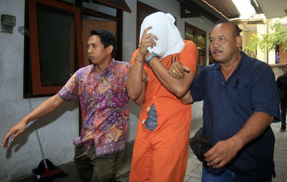 Indonesian police officers escort Tommy Schaefer, center, covering his face, to a hospital for medical check Friday, Aug. 15, 2014. The body of the 62-year-old American woman Sheila von Wiese-Mack was found stuffed inside a suitcase on the Indonesian resort island of Bali, and authorities on Wednesday arrested her daughter Heather Mack and her daughter's boyfriend Schaefer in relation to the death, police said. (AP Photo/Firdia Lisnawati)