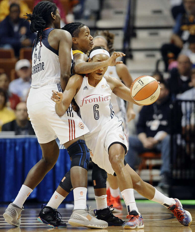 Connecticut Sun's Jasmine Thomas, right, is hit in the face by Chicago Sky's Jamierra Faulkner, center, while dribbling as Sun's Nikki Greene, left, defends during the first half of a WNBA basketball game, Sunday, Sept. 13, 2015, in Uncasville, Conn. (AP Photo/Jessica Hill)