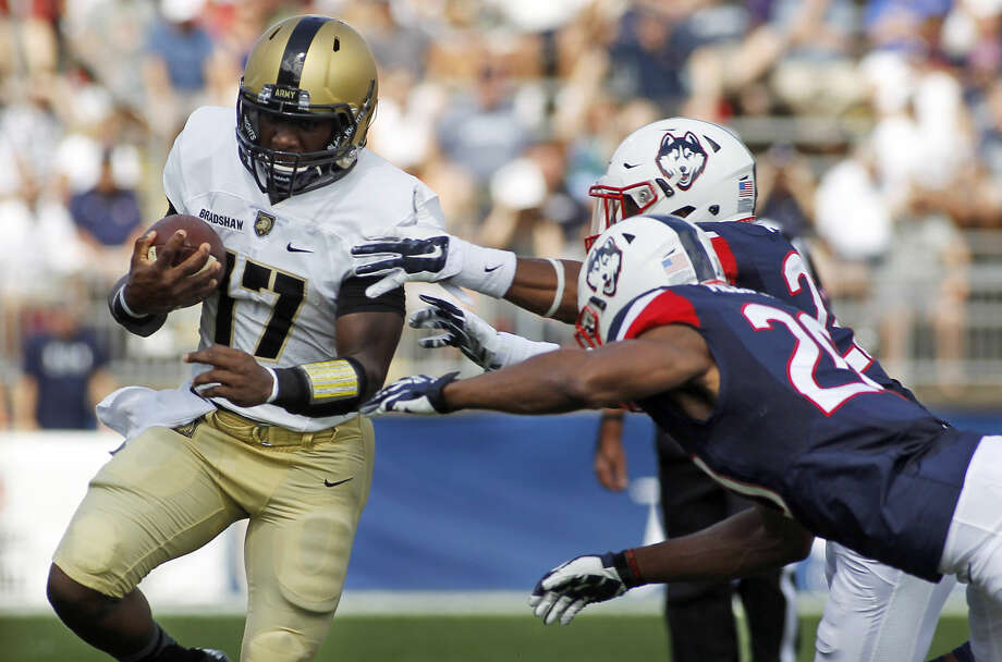 Connecticut safety Andrew Adams, rear right and Obi Melifonwu (20) tackle Army quarterback Ahmad Bradshaw (17) during the first quarter of an NCAA college football game at Rentschler Field, Saturday, Sept. 12, 2015, in East Hartford, Conn. (AP Photo/Stew Milne)