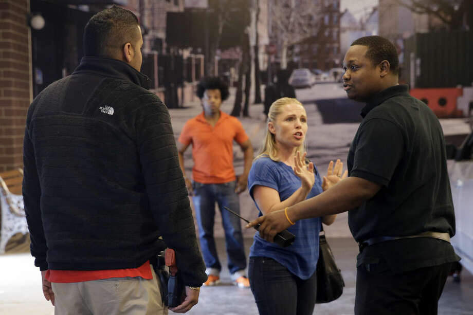 In this Wednesday, Sept. 2, 2015 photo, officers Officer Yani Suri, left, and Dario Henriquez, right, talk to actors Jaimie Kelton, center, and Grant Cooper, background, during a Crisis Intervention Training class at the New York Police Department Police Academy, in New York. A new training for New York City police is combining actors, the mentally ill and psychology experts to better prepare officers responding to people in the throes of a mental crisis. (AP Photo/Mary Altaffer)