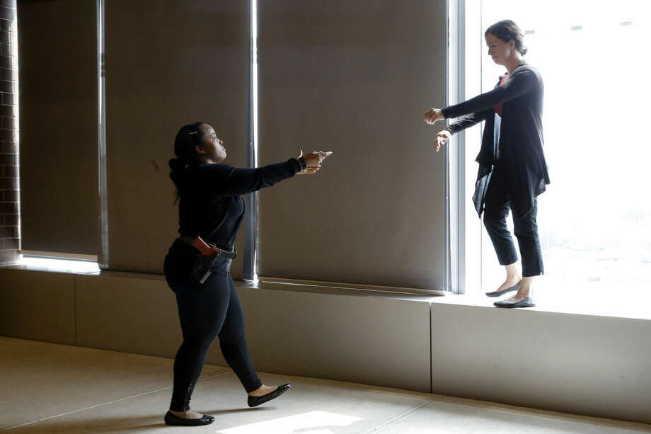 In this Wednesday, Sept. 2, 2015 photo, Sgt. Cecilia Luckie, left, talks actress Erin Shields, off a ledge during a Crisis Intervention Training class at the New York Police Department Police Academy, in New York. A new training for New York City police is combining actors, the mentally ill and psychology experts to better prepare officers responding to people in the throes of a mental crisis. (AP Photo/Mary Altaffer)