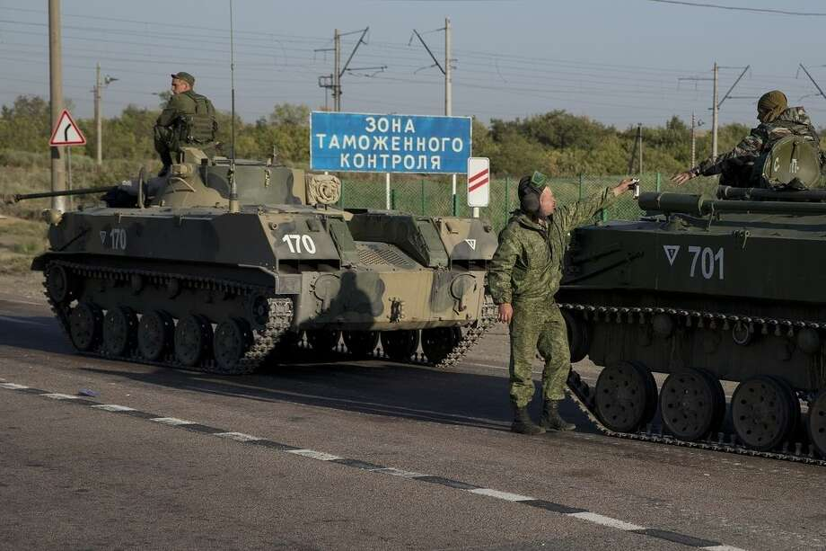 "Russian solders with their several military vehicle gather at the rail road crossing about 30 kilometers (19 miles) from Ukrainian border at Rostov-on-Don region, Russia, early Friday, Aug. 15, 2014. The sigh reads ""Customs control zone"". (AP Photo/Pavel Golovkin)"