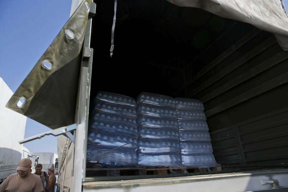 Bottles with water are placed in the back of a truck as Russian Ministry of Emergency Situation decided to show the aid convoy to journalists in Voronezh, about 28 kilometers (17 miles) from Ukrainian border, Rostov-on-Don region, Russia, Friday, Aug. 15, 2014. The Ukrainian government threatened to use all means available to block the convoy if the Red Cross was not allowed to inspect the cargo. Such an inspection would ease concerns that Russia could use the aid shipment as cover for a military incursion in support of the separatists, who have come under growing pressure from government troops. (AP Photo/Pavel Golovkin)