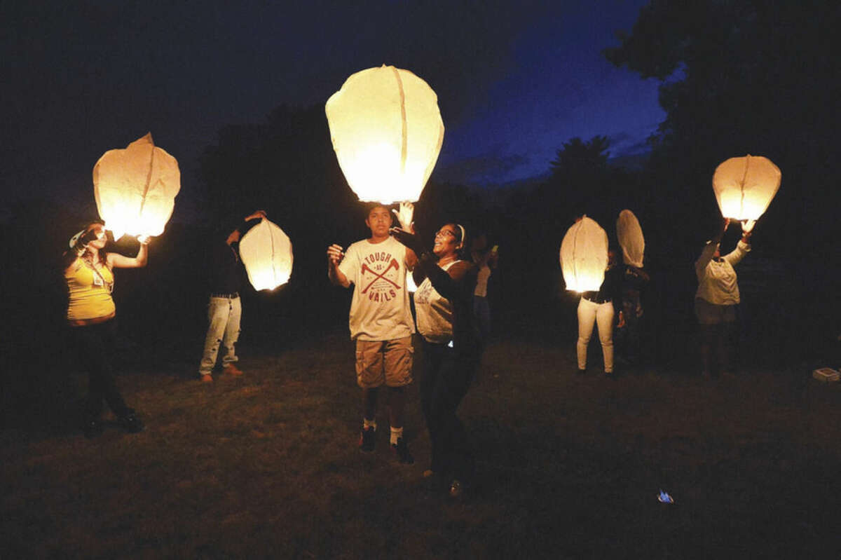 Hour photo/Alex von Kleydorff. Chinese lanterns are released at Union Cemetery in memory of Amos Brown Jr. on the 4-year anniversary of his death.