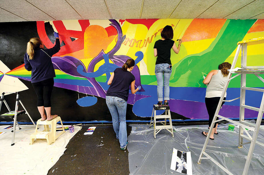 Hour photo / Erik Trautmann Epsilon employees paint a mural at Trailblazers Academy Charter Middle School in Stamford that represents ways school staff help children build skills to heal from trauma they have experienced.