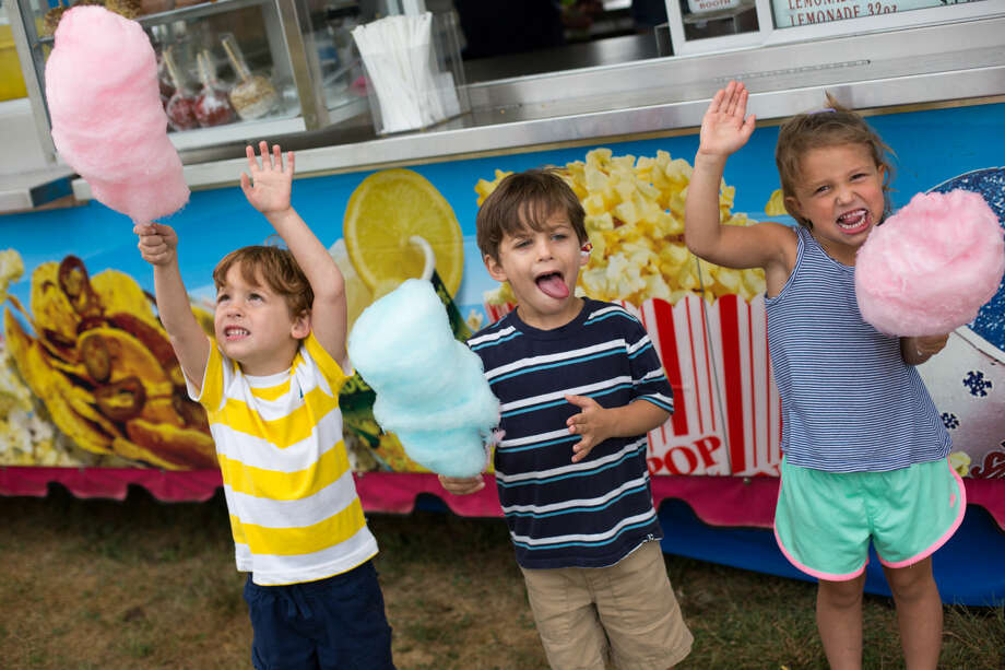 Hour photo/Chris Palermo. Conor, Peter, and Audrey Wolf celebrate over some newly aquired cotton candy at the Oyster Festival Saturday afternoon.