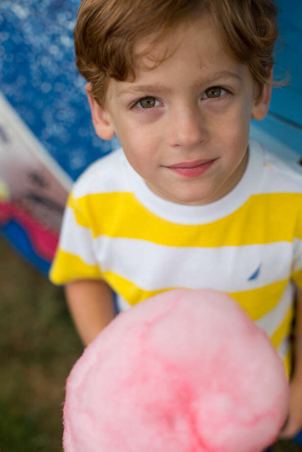 Hour photo/Chris Palermo. Conor Wolf poses for a portrait with his newly aquired cotton candy at the Oyster Festival Saturday afternoon.