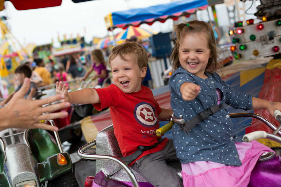 Hour photo/Chris Palermo. Lucy and Lorenzo Doyle wave toward their parents while on one of the rides at the Oyster Festival Saturday afternoon.