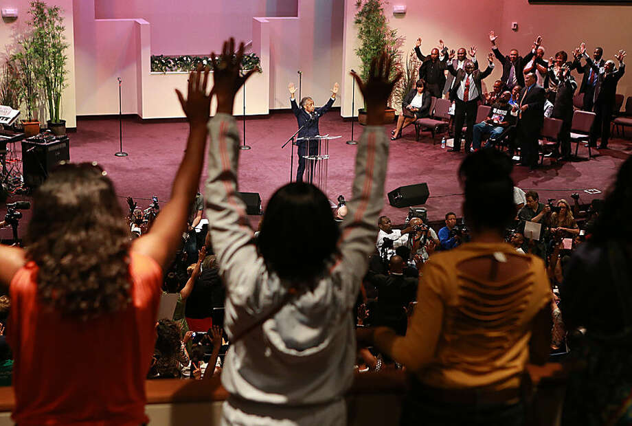 The Rev. Al Sharpton raises his hands with the crowd during a service for the Michael Brown family at the Greater Grace Church in Ferguson, Mo. on Sunday, Aug. 17, 2014. On Saturday, Aug. 9, 2014, a white police officer fatally shot Brown, an unarmed black teenager, in the St. Louis suburb. (AP Photo/St. Louis Post-Dispatch, Christian Gooden)