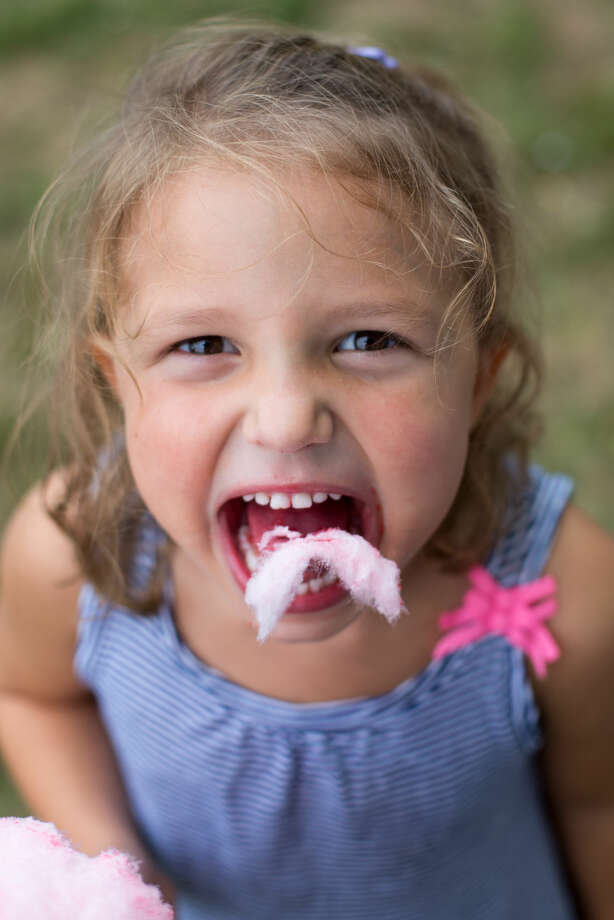 Hour photo/Chris Palermo. Audrey Wolf takes a bite out of her cotton candy at the Oyster Festival Saturday afternoon.
