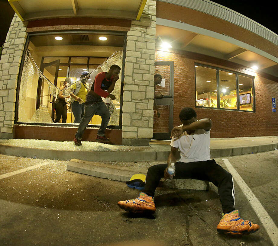 In this photo taken with a fisheye lens, people leave a McDonald's restaurant after taking refuge from tear gas Sunday, Aug. 17, 2014, as they staged a protest for Michael Brown, who was killed by a police officer last Saturday in Ferguson, Mo. As night fell Sunday in Ferguson, another peaceful protest quickly deteriorated after marchers pushed toward one end of a street. Police attempted to push them back by firing tear gas and shouting over a bullhorn that the protest was no longer peaceful. (AP Photo/Charlie Riedel)