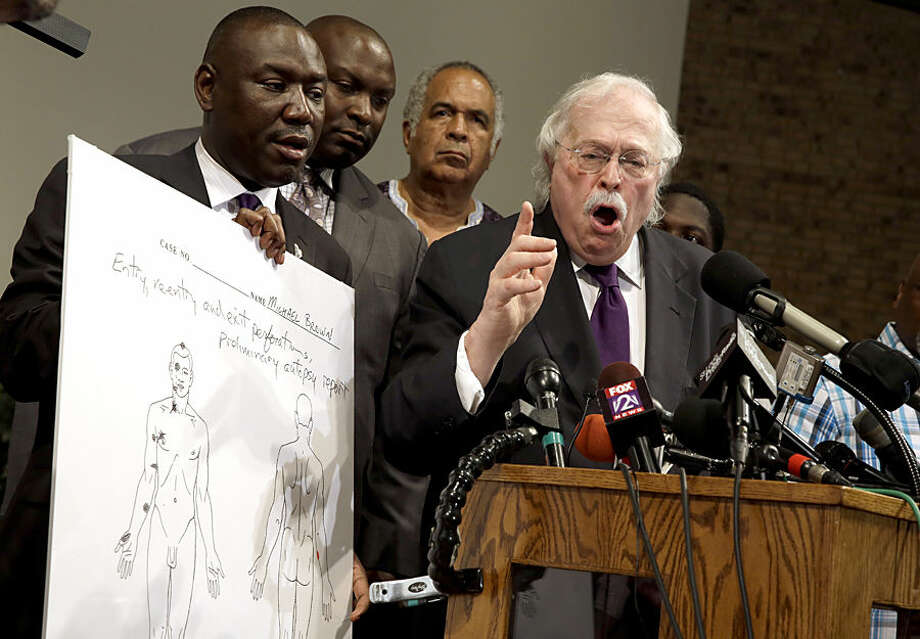 Dr. Michael Baden, right, speaks as Brown family attorney Benjamin Crump, left, holds a diagram produced during a second autopsy done on 18-year-old Michael Brown Monday, Aug. 18, 2014, in St. Louis County, Mo. The independent autopsy shows Brown was shot at least six times. (AP Photo/Jeff Roberson)