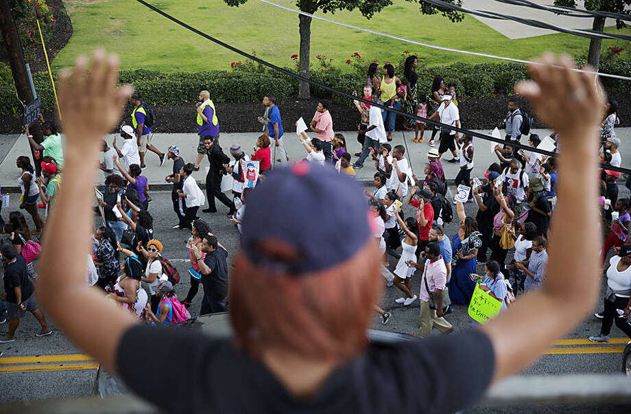 A waitress holds up her hands while watching from a restaurant balcony as protestors march in response to the fatal shooting of Michael Brown, Monday, Aug. 18, 2014, in Atlanta. Hundreds of demonstrators gathered in downtown Atlanta to protest the shooting death of Brown, an unarmed man who was fatally shot by a police officer in Ferguson, Missouri. (AP Photo/David Goldman)
