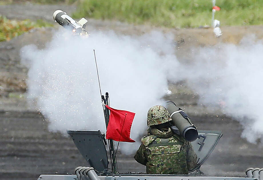 A member of the Japan Ground Self-Defense Force launches a hand-held anti-tank rocket during an annual live firing exercise at Higashi Fuji range in Gotemba, southwest of Tokyo, Tuesday, Aug. 19, 2014. (AP Photo/Shizuo Kambayashi)