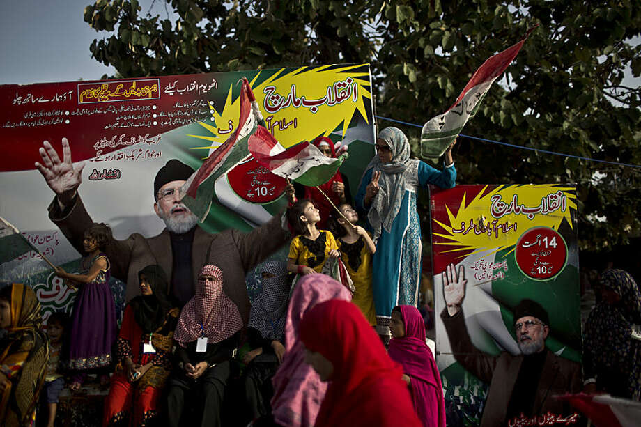 Supporters of fiery anti-government cleric Tahir-ul-Qadri, his images seen at background, take part in a protest, in Islamabad, Pakistan, Monday, Aug. 18, 2014. Qadri led massive rallies Saturday in Pakistan's capital, demanding Prime Minister Nawaz Sharif step down over alleged fraud in last year's election in front of thousands of protesters. (AP Photo/Muhammed Muheisen)