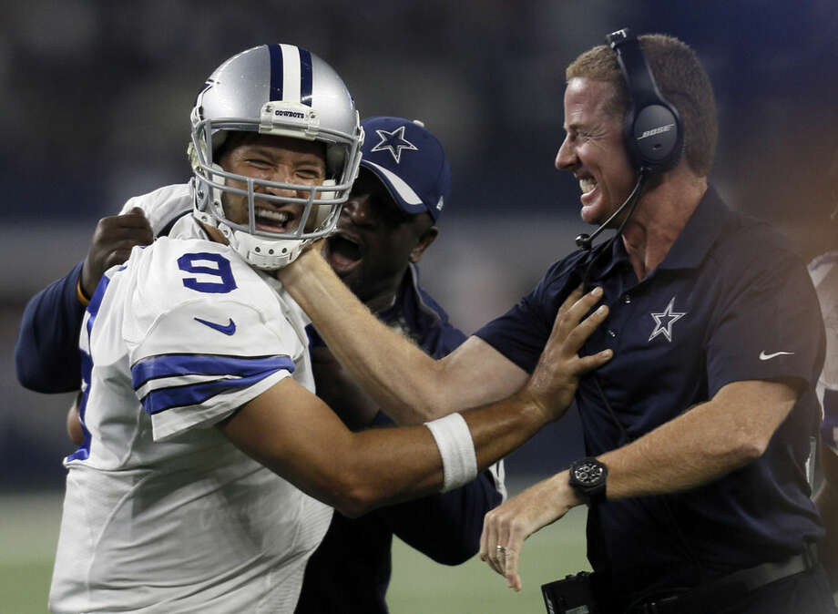 Dallas Cowboys quarterback Tony Romo and head coach Jason Garrett celebrate a last minute touchdown pass to tight end Jason Witten (82) to win against the New York Giants during the second half of an NFL football game Sunday, Sept. 13, 2015, in Arlington, Texas. Cowboys won 27-26. (AP Photo/Brandon Wade)