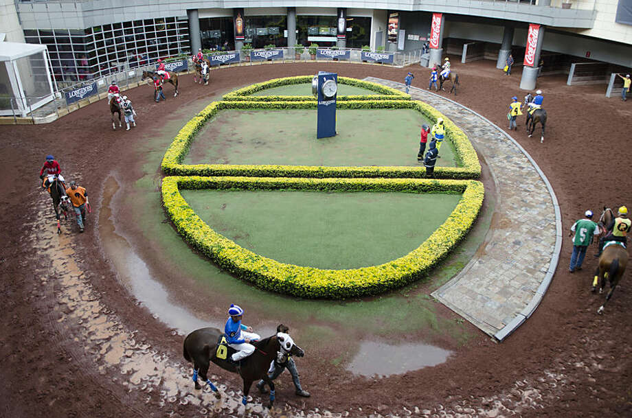 In this July 4, 2014 photo, jockeys get ready to ride to their starting posts before a race at the Hippodrome of the Americas in Mexico City. There are approximately 200 registered jockeys that are skilled enough to ride a half-ton race horse in Mexico. (AP Photo/Sean Havey)