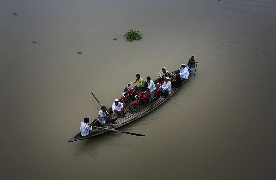 Villagers sail on a boat through a flood-affected area in Ashigarh village, about 70 kilometers (44 miles) east of Gauhati, India, Thursday, Aug. 19, 2014. Heavy rainfall for the past few days has affected several districts of Assam state, flooding dozens of villages and displacing thousands. (AP Photo/Anupam Nath)