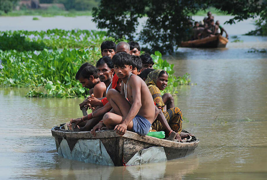 Flood affected Indian villagers sit in country boats as they try to move to safer places in Harinarayanpur village in Barabanki district of Uttar Pradesh state, India, Monday, Aug. 18, 2014. The death toll from three days of flooding and torrential rain in Nepal and India rose to more than 180 people Monday, as relief teams sent food, tents and medicine to prevent any outbreaks of disease. (AP Photo/Sanjay Sonkar)