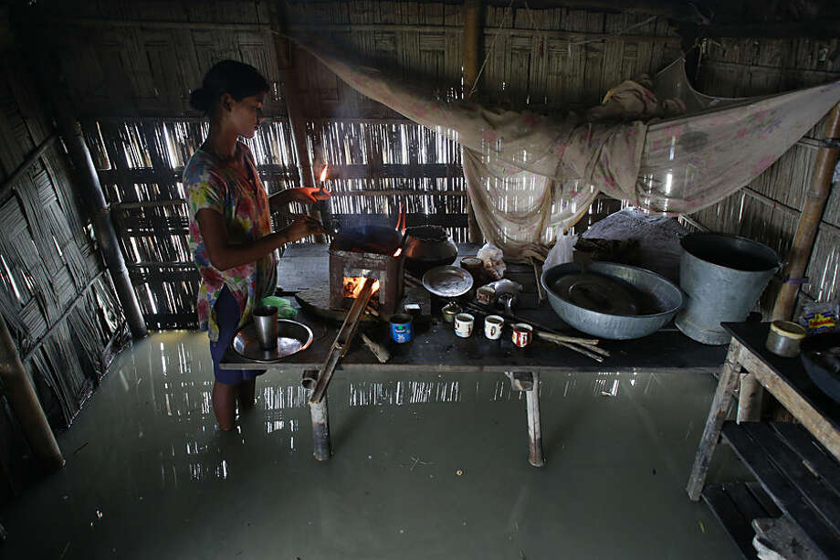 Dupura Akhtar, cooks inside her flood-affected house in Ashigarh village, about 70 kilometers (44 miles) east of Gauhati, India, Thursday, Aug. 19, 2014. Heavy rainfall for the past few days has affected several districts of Assam state, flooding dozens of villages and displacing thousands. (AP Photo/Anupam Nath)