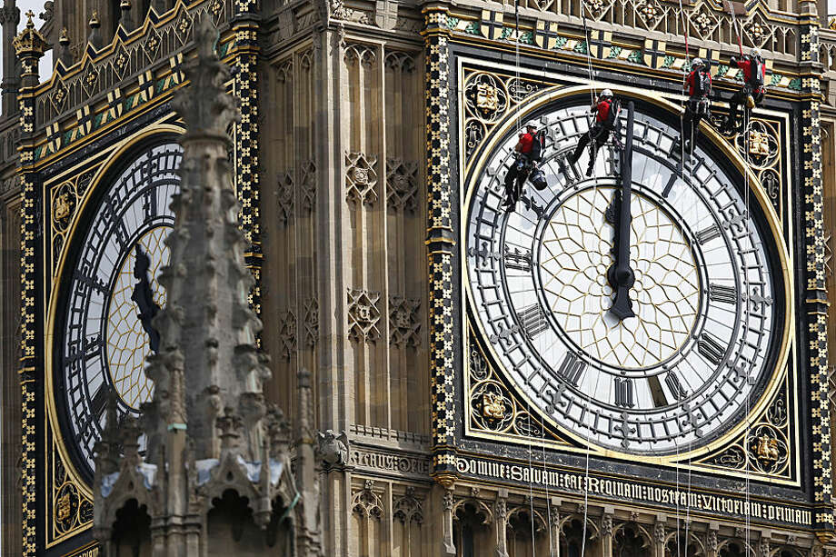 Workers hang outside the clock face as they clean the Big Ben clocktower of the Houses of Parliament in London, Monday, Aug. 18, 2014. (AP Photo/Sang Tan)