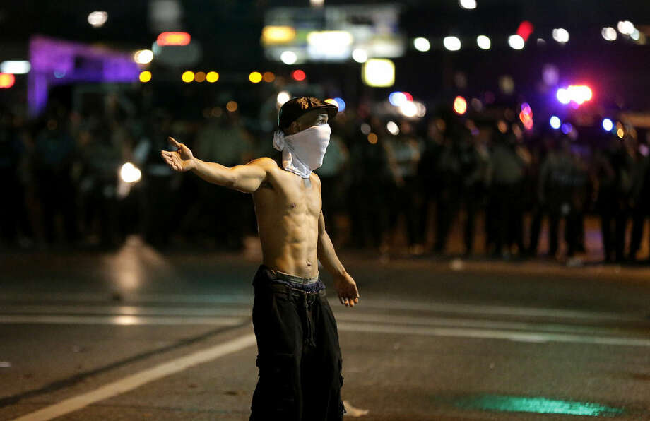 A man stands in the street during a protest Monday, Aug. 18, 2014, for Michael Brown, who was killed by a police officer Aug. 9 in Ferguson, Mo. Brown's shooting has sparked more than a week of protests, riots and looting in the St. Louis suburb. (AP Photo/Charlie Riedel)