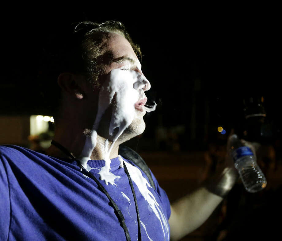 A man tries to recover after being treated for getting hit with tear gas during a protest Monday, Aug. 18, 2014, for Michael Brown, who was killed by police Aug. 9 in Ferguson, Mo. Brown's shooting has sparked more than a week of protests, riots and looting in the St. Louis suburb. (AP Photo/Charlie Riedel)