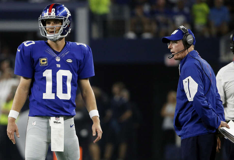 In this photo taken Sunday, Sept. 13, 2015,New York Giants quarterback Eli Manning (10) and head coach Tom Coughlin stands on the field late in the second half of an NFL football game against the Dallas Cowboys in Arlington, Texas. New York was about to put a damper on another festive prime-time opener Sunday night. Instead, the Giants were stunned 27-26 on a winning drive by Tony Romo after Manning admittedly made a crucial mistake. (AP Photo/Tony Gutierrez)