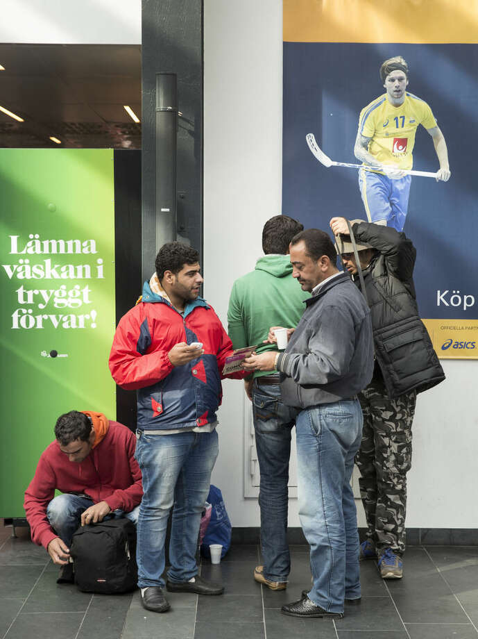 In this image taken Thursday Sept. 10, 2015 newly arrived migrants swap sim cards in their phones at the Central Station in Malmo Sweden before calling home. The bleary-eyed migrants arriving in Malmo's glass-and-steel train station agreed on one thing: Sweden was a better place to go than Denmark, which has cut welfare benefits for refugees. (Ola Torkelsson/TT via AP) SWEDEN OUT