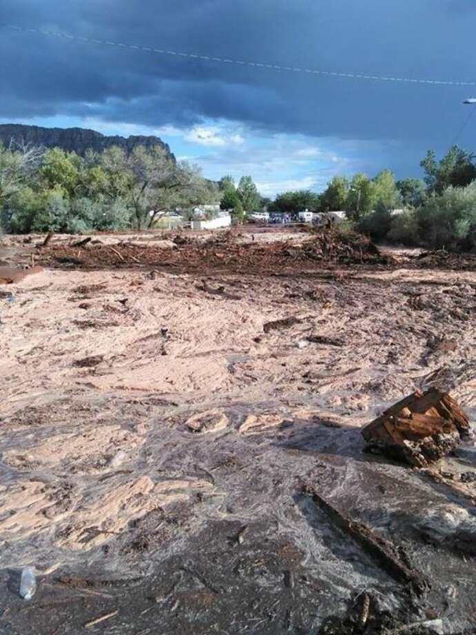 Debris and water cover the ground after a flash flood Monday, Sept. 14, 2015, in Hildale, Utah. Authorities say multiple people are dead and others missing after a flash flood ripped through the town on the Utah-Arizona border Monday night. (Mark Lamont via AP) MANDATORY CREDIT