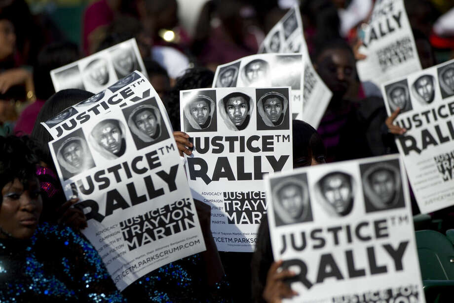 FILE - This April 1, 2012 file photo shows members of the audience holding signs of support as thousands gathered in downtown Miami demanding justice for Trayvon Martin during a rally that featured national civil rights leaders. The rally comes a day after thousands marched through Sanford, the Florida town where 17-year-old Martin was shot and killed in February. Protesters say they will continue holding marches and rallies until an arrest is made. Eric Holder, who is leading the federal response to the racial turmoil in Ferguson, Missouri, talks about the nation's civil rights struggles in a way none of the 81 previous U.S. attorneys general could _ by telling his own family story. (AP Photo/J Pat Carter, File)