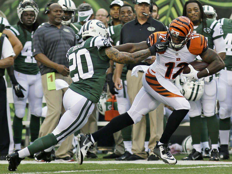 Cincinnati Bengals wide receiver Mohamed Sanu (12) catches a pass against New York Jets cornerback Kyle Wilson (20) in the first half of an NFL preseason football game, Saturday, Aug. 16, 2014, in Cincinnati. (AP Photo/Tony Tribble)