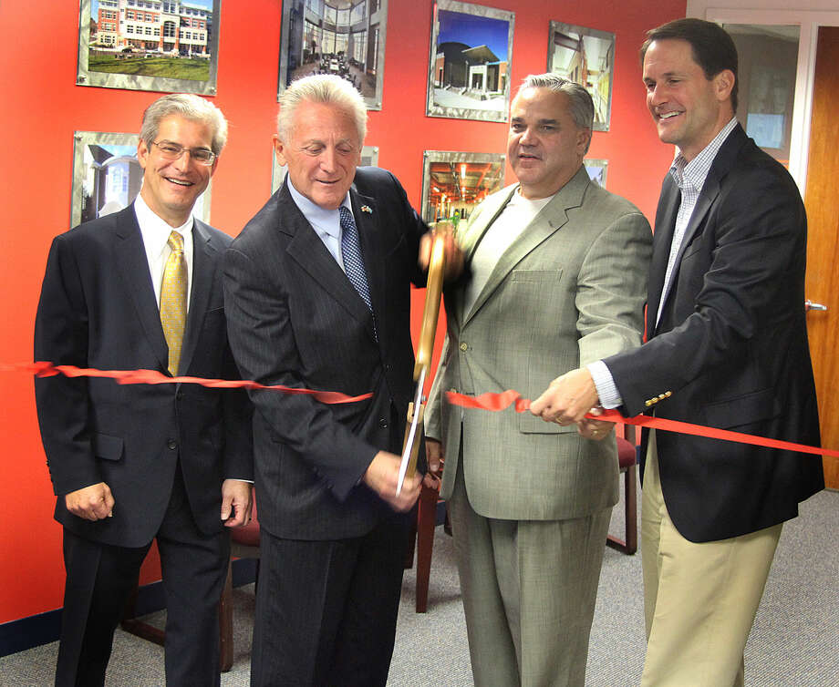 Hour photo/Chris Bosak KBE Builders celebrated its expansion into Norwalk on Tuesday with a ribbon cutting at its offices at 200 Connecticut Ave. Cutting the ribbon are (left to right) Allan Kleban of KBE, Norwalk Mayor Harry Rilling, Michael Kolakowski of KBE and Congressman Jim Himes.