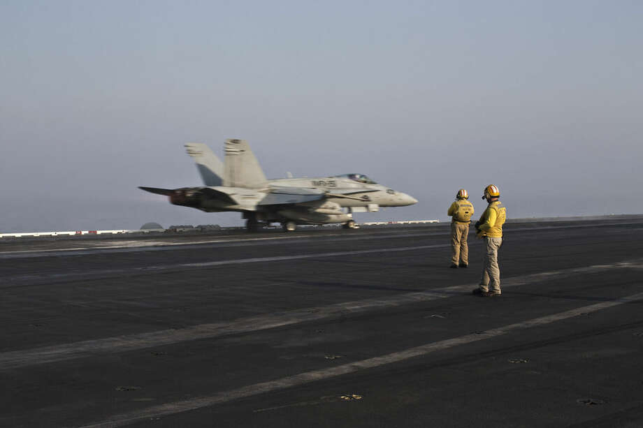 In this Thursday, Sept. 10, 2015 photo, plane directors, wearing yellow jerseys, oversee the takeoff of a U.S. Marine fighter jet aircraft aboard the USS Theodore Roosevelt aircraft carrier. Pilots onboard have flown missions into both Iraq and Syria, part of the over 6,800 airstrikes carried out since August 2014. Some 20 percent of all coalition strikes come from aircraft launched from the nuclear-powered Roosevelt.(AP Photo/Marko Drobnjakovic)