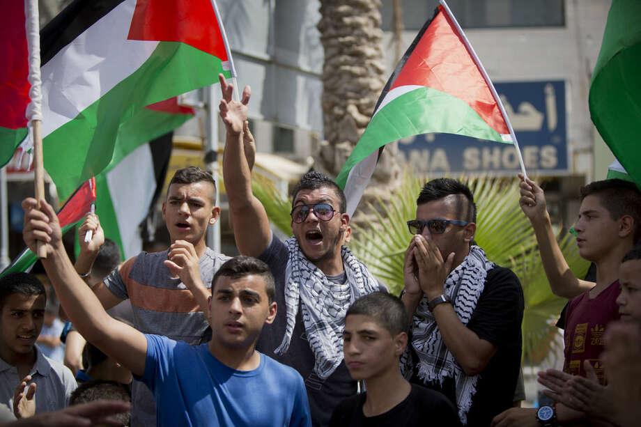 Palestinians chant slogans in solidarity with protesters at the Al-Aqsa mosque compound in Jerusalem's Old City, during a demonstration in the West Bank town of al-Ram, north of Jerusalem, Tuesday, Sept. 15, 2015. Israeli police clashed with Palestinian protesters Tuesday in a third straight day of unrest at Jerusalem's most sensitive holy site. (AP Photo/Majdi Mohammed)