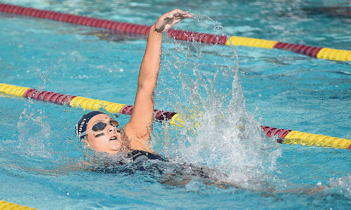 Wilton's Emma Holmquist competes in the backstroke portion of the 200 IM during Wednesday's season-opening meet against New Canaan at the Wilton Y pool. (Hour photo/John Nash)