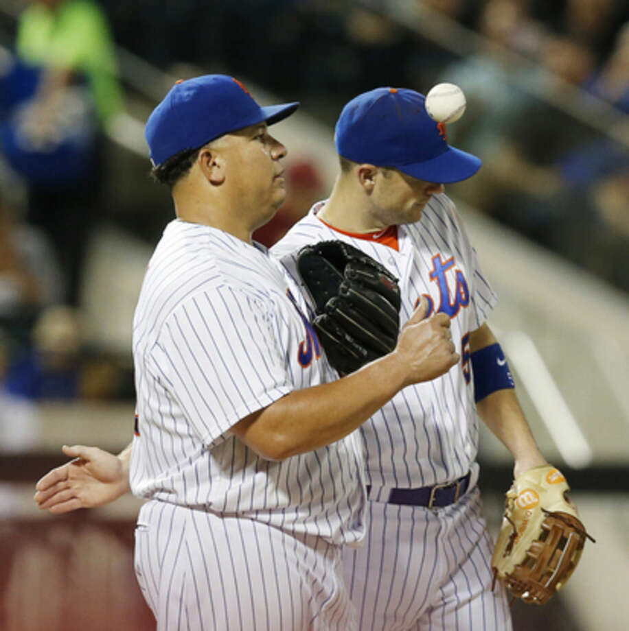 New York Mets third baseman David Wright, right, consoles starting pitcher Bartolo Colon before Mets manager Terry Collins removed Colon during the sixth inning of a baseball game against the Miami Marlins in New York, Wednesday, Sept. 16, 2015. (AP Photo/Kathy Willens)