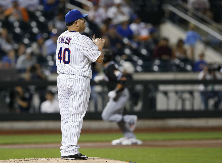 New York Mets starting pitcher Bartolo Colon (40) reacts after allowing a fourth-inning solo home run to Miami Marlins' Martin Prado, rear, during a baseball game in New York, Wednesday, Sept. 16, 2015. (AP Photo/Kathy Willens)