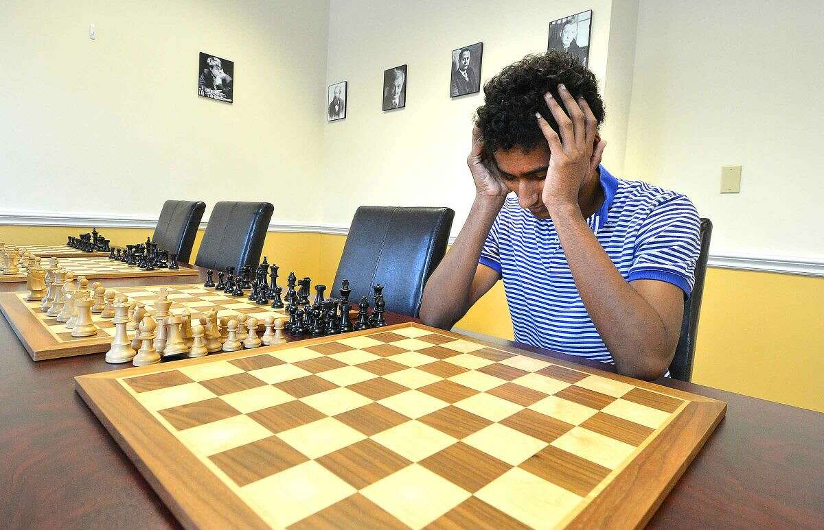 """Hour Photo/Alex von Kleydorff With an empty chess board in front of him, Kapil Chandran concentrates on remebering his opponents moves and where he will move next as he plays a """"blind"""" game of chess with multiple opponents at The Chess Club of Fairfield County"""
