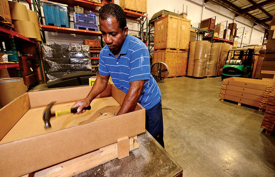 Hour photo / Erik Trautmann Pierre Lodge assembles containers for Commerce Packaging who are celebrating 60 years in business.