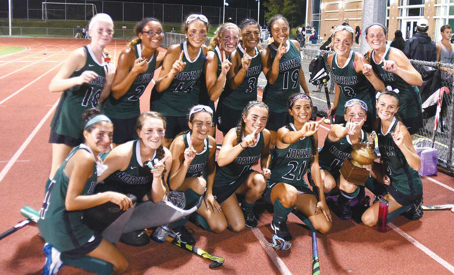 Hour photo/John Nash - Members of the Norwalk High field hockey team celebrate their 8-0 win over Brien McMahon with the trophy that goes to the winner of the annual contest.