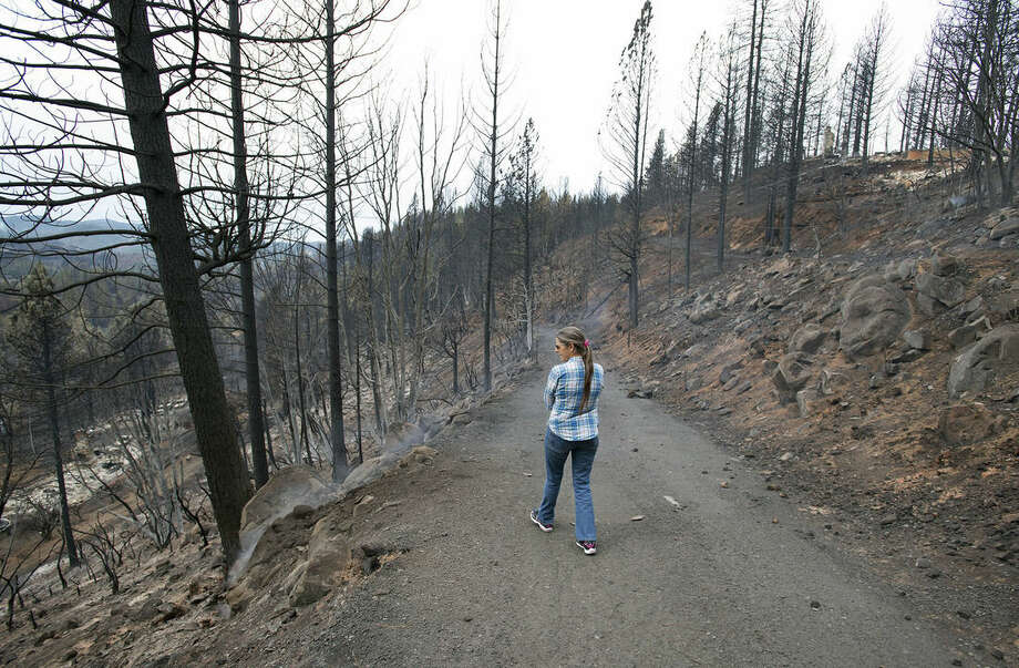 Patti Murphy walks down a road toward her burned home in Cobb on Tuesday, September 15, 2015, in Lake County, Calif. The fire that sped through Middletown and other parts of rural Lake County, less than 100 miles north of San Francisco, has continued to burn since Saturday despite a massive firefighting effort. (Randy Pench/The Sacramento Bee via AP) MAGS OUT; LOCAL TELEVISION OUT (KCRA3, KXTV10, KOVR13, KUVS19, KMAZ31, KTXL40); MANDATORY CREDIT