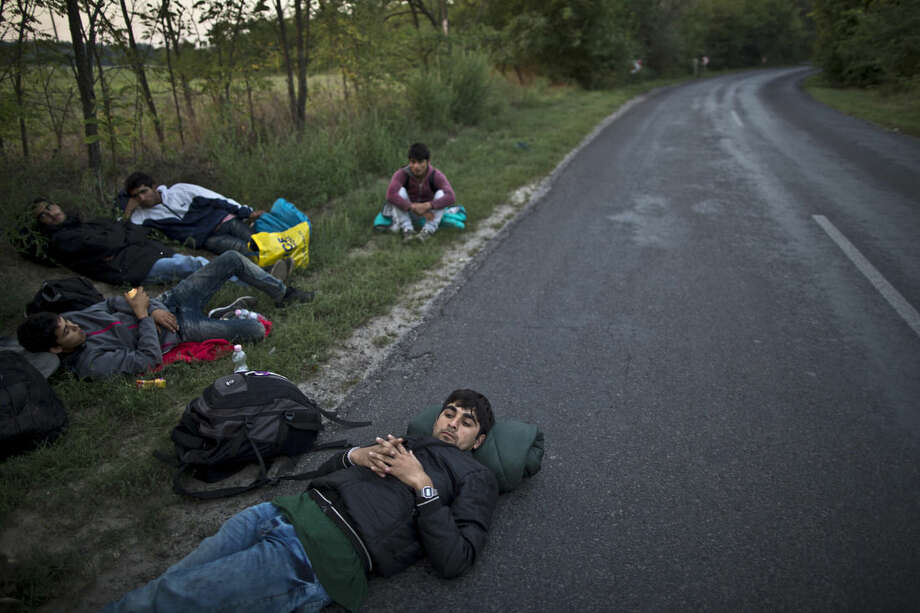 Afghan migrants rest on a roadside near Hungary's border fence with Serbia, in Asotthalom, southern Hungary, Wednesday, Sept. 16, 2015. Small groups of migrants are continuing to sneak into Hungary from Serbia, a day after the country sealed its border and began arresting asylum-seekers trying to breach the new razor-wire barrier. (AP Photo/Muhammed Muheisen)