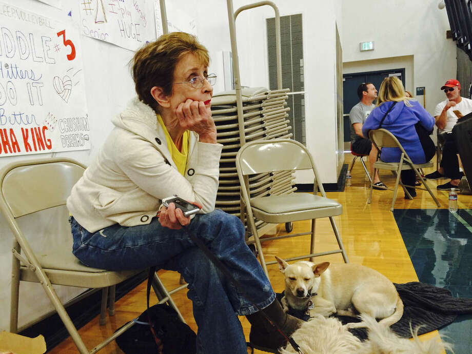 Nell Boyer, a real estate agent, waits at Lower Lake High School Tuesday, Sept. 15, 2015, to be escorted back to her burned-down home to find and feed her chickens and cats in Lower Lake, Calif. With her are her dogs, Coby and Winston. Lower Lake, a remote, mountainous county in Northern California best known for its freshwater lake is now known as the place devastated by three major drought-fueled wildfires this summer. (AP Photo/Janie Har)