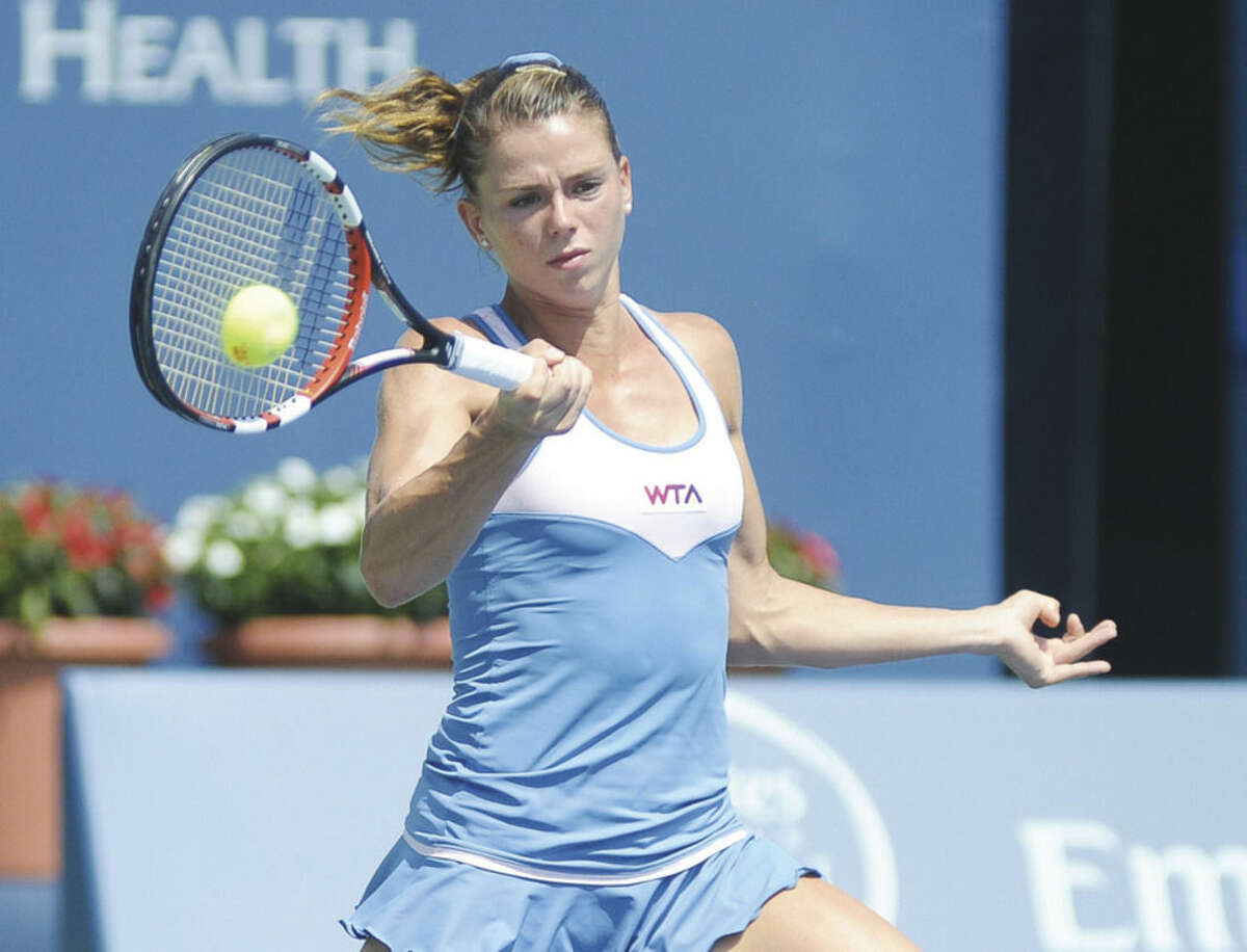 Hour photo/John Nash Camila Giorgi hits a running forehand winner during her 6-4, 6-2 upset victory over Caroline Wozniacki during Wednesdays' Round of 16 match at the Stadium Court at the Connecticut Open Tennis Tournament at Yale University in New Haven.